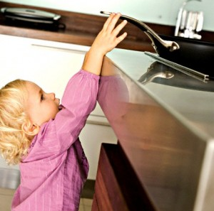 Little girl in kitchen trying to catch a frying pan on stove --- Image by © Pascal Broze/Onoky/Corbis